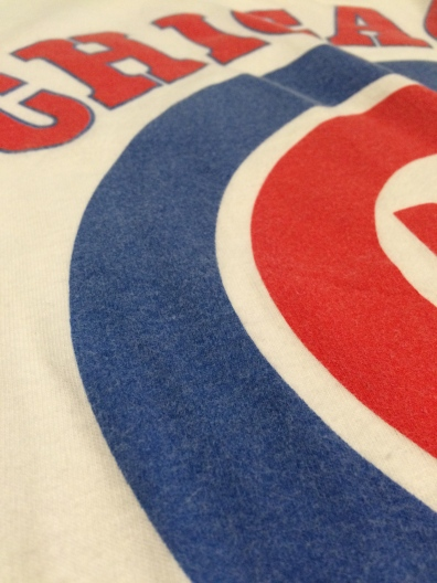 See how the white material has begun to blend into the blue Cubs logo? The logo is no longer a crisp blue. It is faded with white lint material.